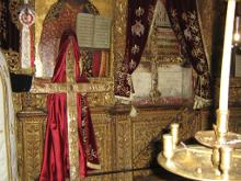 В центре в кресте размещены частицы Животворящаго Креста Господня. Справа в ковчеге в виде креста помещены Узы Христовы.